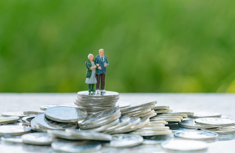 Ein Rentnerpaar schaut auf einen Münzberg
