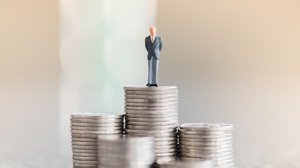Mann steht auf Geldtürmen, die seine Rente symbolisieren