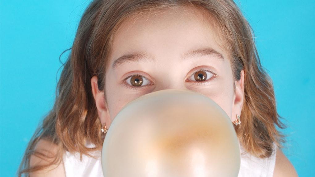 Mädchen macht eine Kaugummiblase