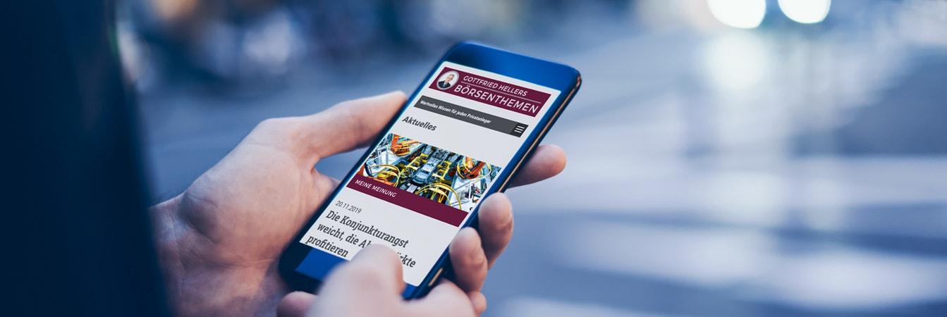 Mann schaut sich den neuen Webauftritt von Gottfried Heller auf dem Handy an